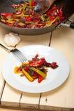 油煎的辣椒和菜在铁锅平底锅 免版税库存照片