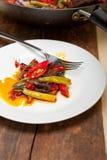 油煎的辣椒和菜在铁锅平底锅 免版税库存图片