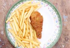 油煎的金黄鸡腿用炸薯条 免版税库存照片