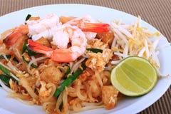 油煎的面条泰国样式用大虾,混乱油炸物面条用在padthai样式的虾在桌上 白色正面图的孤立,棕色ba 库存照片