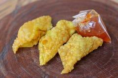 油煎的饺子,中国菜用在塑料袋的调味汁在木桌上 免版税库存照片