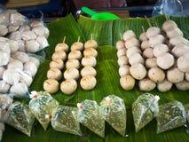 油煎的香肠和油煎的丸子从猪肉 在香蕉叶子上准备好待售在新鲜市场上,泰国街道食物 免版税库存照片