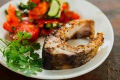 油煎的鱼和沙拉在一块白色板材 库存照片