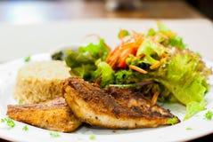 油煎的鱼排用沙拉和炒饭 免版税库存图片