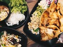 油煎的鱼服务与新鲜蔬菜 免版税库存图片