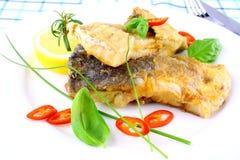 油煎的鱼片用柠檬,在白色板材的辣椒切片 免版税图库摄影