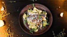 油煎的鱼用土豆和菜在一张木背景顶视图 免版税库存图片