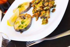 油煎的鱼用在板材的蘑菇 免版税库存图片