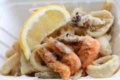 油煎的鱼用外带的虾和切片柠檬 免版税库存图片