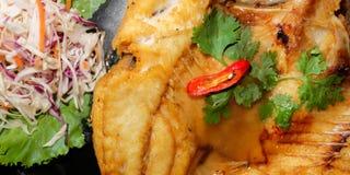油煎的鱼用新鲜的草本和甜辣调味汁 免版税库存图片