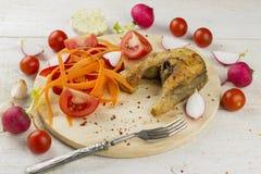 油煎的鱼用红萝卜,蕃茄,大蒜,庭院萝卜 免版税库存图片