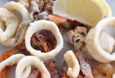 油煎的鱼用虾和柠檬切片 免版税库存图片