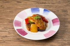 油煎的鱼用辣椒、黄瓜和茄子在白色板材 库存图片
