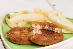 油煎的鱼肉汉堡服务用在板材的炸薯条 免版税库存照片