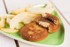 油煎的鱼肉汉堡服务用在板材的炸薯条 免版税库存图片