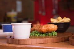 油煎的鱼wih饼和芯片在背景中 免版税库存照片