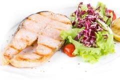 油煎的鲑鱼排用沙拉和柠檬在白色板材孤立 关闭 库存照片