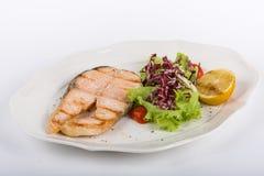 油煎的鲑鱼排用沙拉和柠檬在白色板材孤立 图库摄影