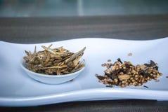 油煎的鲥鱼用在陶瓷白色板材的混合香料在木背景 库存图片