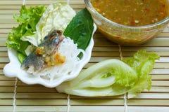 油煎的鲭鱼服务用煮沸的泰国米细面条 免版税库存照片