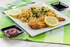 油煎的鳕鱼用柠檬和炒米 免版税库存照片
