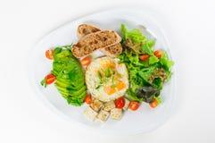 油煎的鹌鹑蛋、鲕梨、沙拉、西红柿、豆腐和面包在被隔绝的白色板材 库存图片