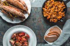 油煎的黄蘑菇、鱼在板材,蕃茄和面包自由空间 库存照片