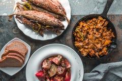 油煎的黄蘑菇、鱼在板材,蕃茄和面包 免版税库存照片