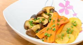 油煎的什塔克菇、红萝卜和土豆用黄油调味 免版税库存图片