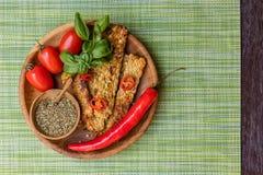 油煎的tempeh、辣椒、新鲜的西红柿、蓬蒿草本的叶子、混合和在木罐的海盐有在a的木匙子的 库存图片