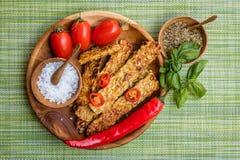 油煎的tempeh、辣椒、新鲜的西红柿、蓬蒿草本的叶子、混合和在木罐的海盐有在a的木匙子的 库存照片