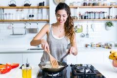 油煎葱的少妇入平底锅在厨房里 免版税图库摄影