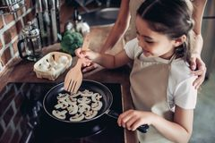 油煎蘑菇的女儿和母亲 免版税图库摄影