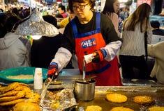 油煎Bindae tteok或绿豆蛋糕的妇女在Gwangjang食品批发市场 库存图片