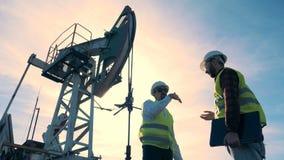 油田工作者在油塔背景,底视图谈话 股票视频