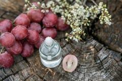 油精华和葡萄在木背景 theraty的芳香 免版税库存照片