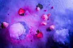 油罐顶部角钢现代视图点心展示或杯红色白色鸡尾酒和烟或干冰蒸汽,草莓莓在黑暗铸造 免版税库存图片
