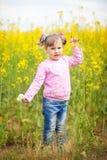 油菜籽的领域的一个小女孩与一束的春黄菊 免版税库存图片