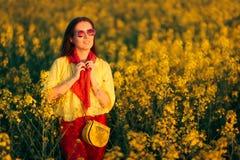 油菜籽花田的现代凉快的时尚妇女 免版税图库摄影