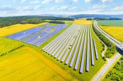 油菜籽领域的太阳能发电厂 免版税库存图片