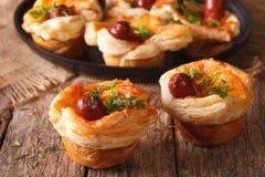 油酥点心小圆面包与香肠和乳酪特写镜头的 水平 免版税库存图片