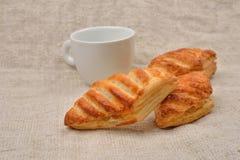 油酥点心用与一杯咖啡的果酱近在黄麻backgro 免版税库存照片