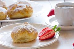 油酥点心蓬松小圆面包与草莓装填和咖啡的 库存照片