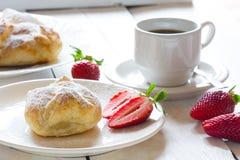 油酥点心蓬松小圆面包与草莓装填和咖啡的 免版税库存照片