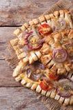 油酥点心饼有红洋葱和蕃茄垂直的顶视图 免版税图库摄影