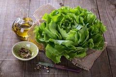 黄油莴苣和油在土气背景 免版税库存照片