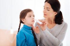 治疗一个连续鼻子的爱恋的母亲她的孩子 免版税库存照片