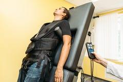 治疗人的脊椎补救物理疗法的人通过舒展用在诊所的特别医疗设备 库存照片