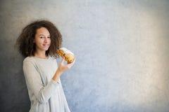 治疗吃新月形面包的卷发女孩对墙壁 免版税库存照片