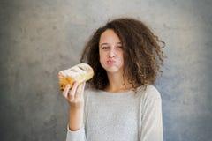 治疗吃新月形面包的卷发女孩对墙壁 库存照片